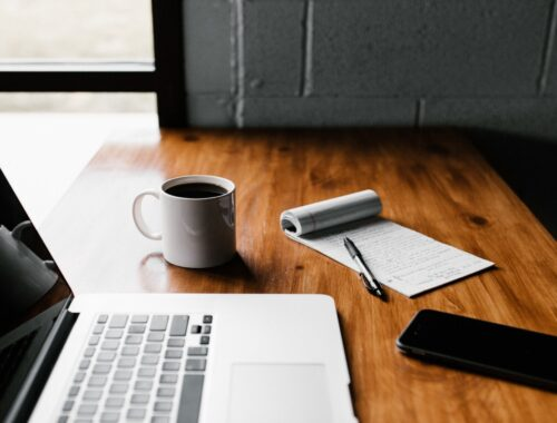computer on a wooden table with a coffee mug and a notebook